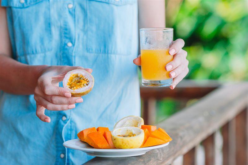 uma mulher comendo a poupa do maracujá e tomando um suco na cor laranja.