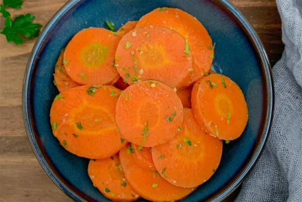 Fatias de cenoura temperadas e dispostas em um prato azul