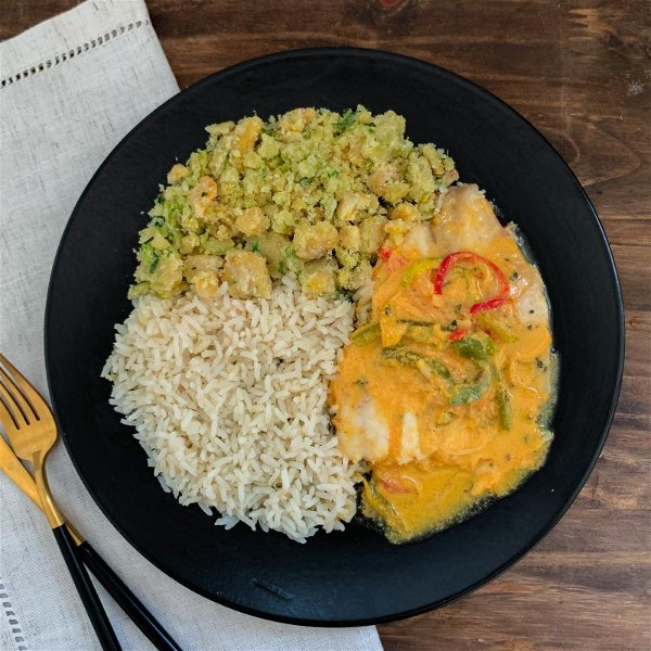 Prato com arroz, moqueca de tilapia e farofa de banana