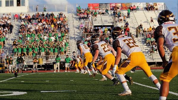 Jogadores de futebol americano alinhados em campo