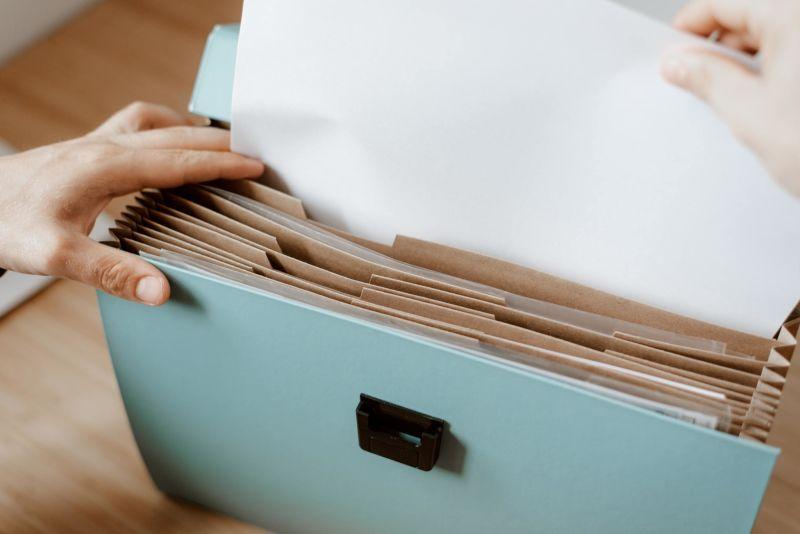Mãos de pessoa organizando documentos em pasta.