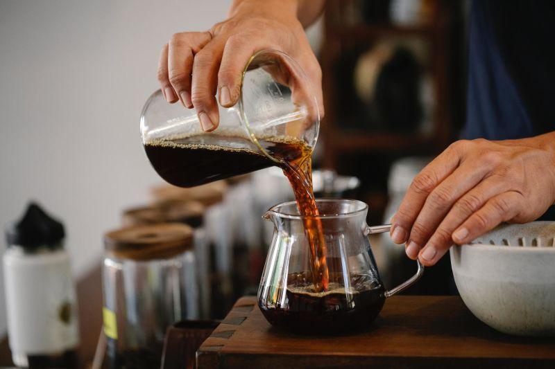 Mãos de pessoa preparando café.