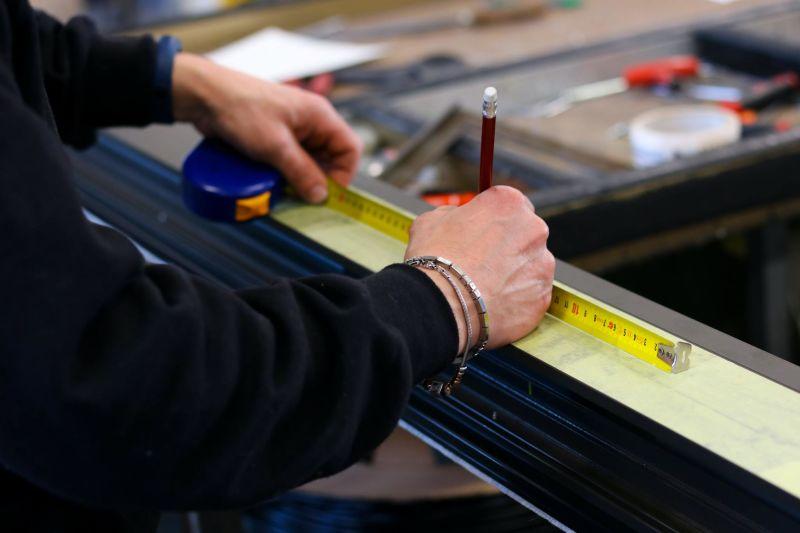 Mão de pessoa segurando fita métrica e lápis.